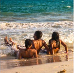 three friends at the beach sitting in the water enjoying the fresh air