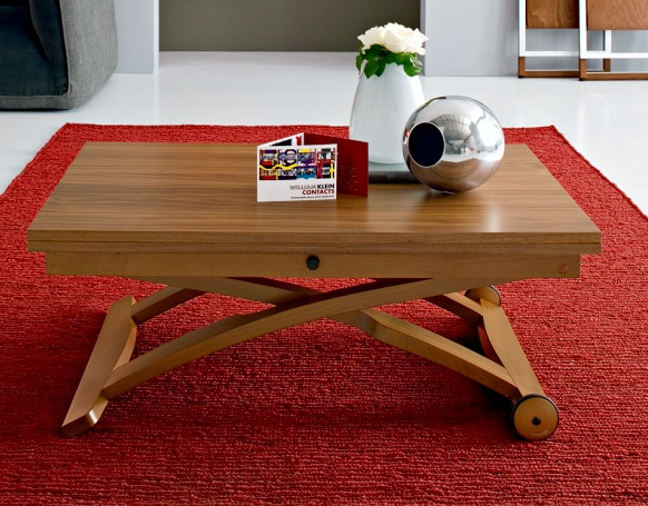 image of furniture showing an expandable coffee table on a rug defining a space on the floor with some decorating items on top