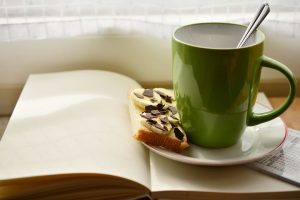 image of a cup of hot tea and a snack on a saucer sitting on top of an open book