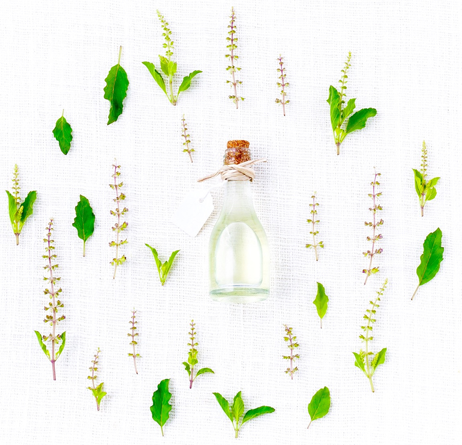 image of essential oil leaves in a circle around a pretty bottle of oil