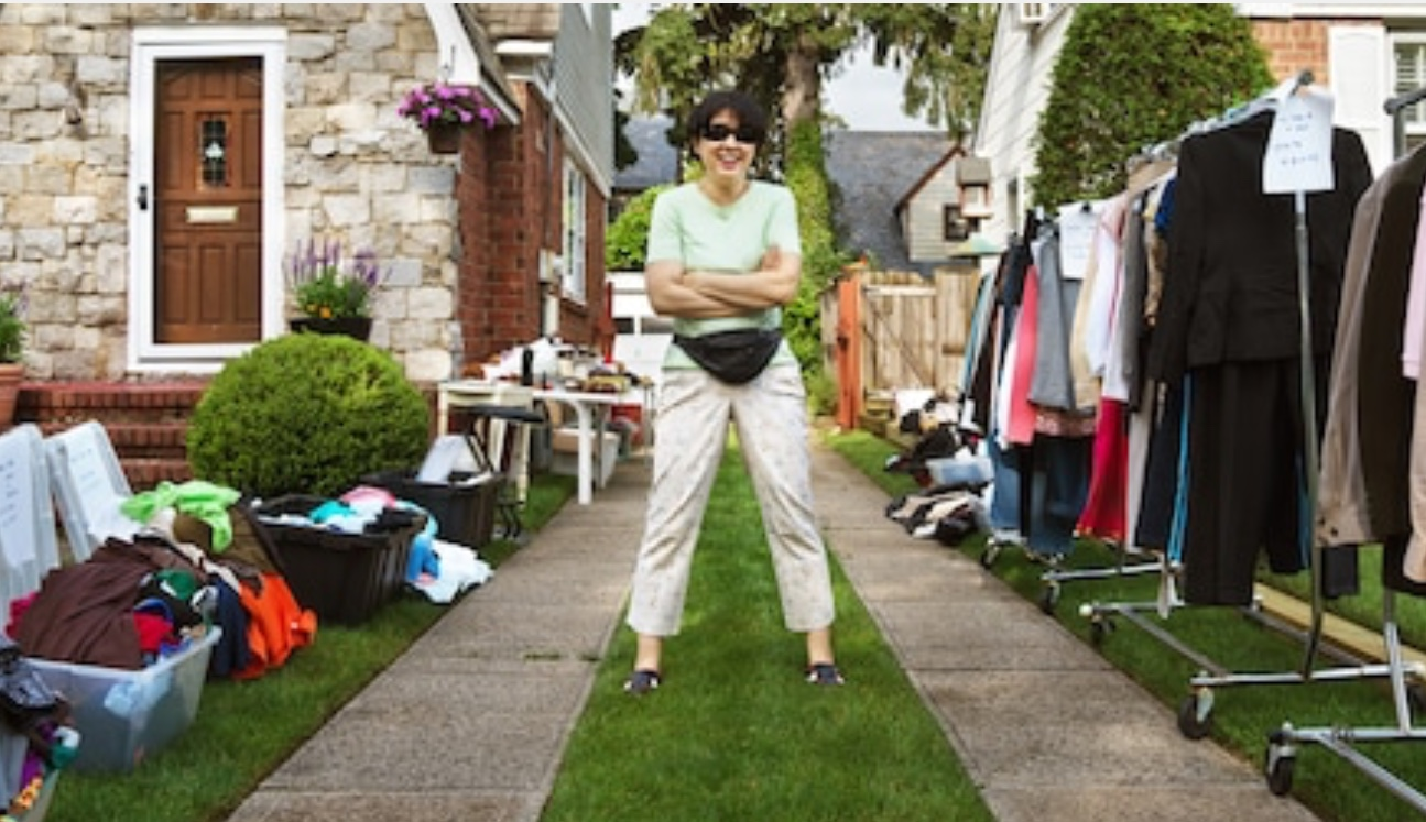 image of a person standing in a lawn with garage sale stuff