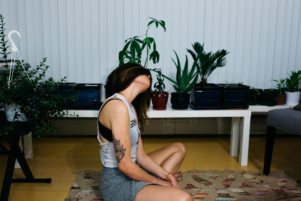 Image of sitting girl with her eyes covered so she can sense the different placements of the houseplants.