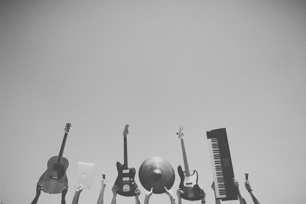 image of friends holding up musical instruments