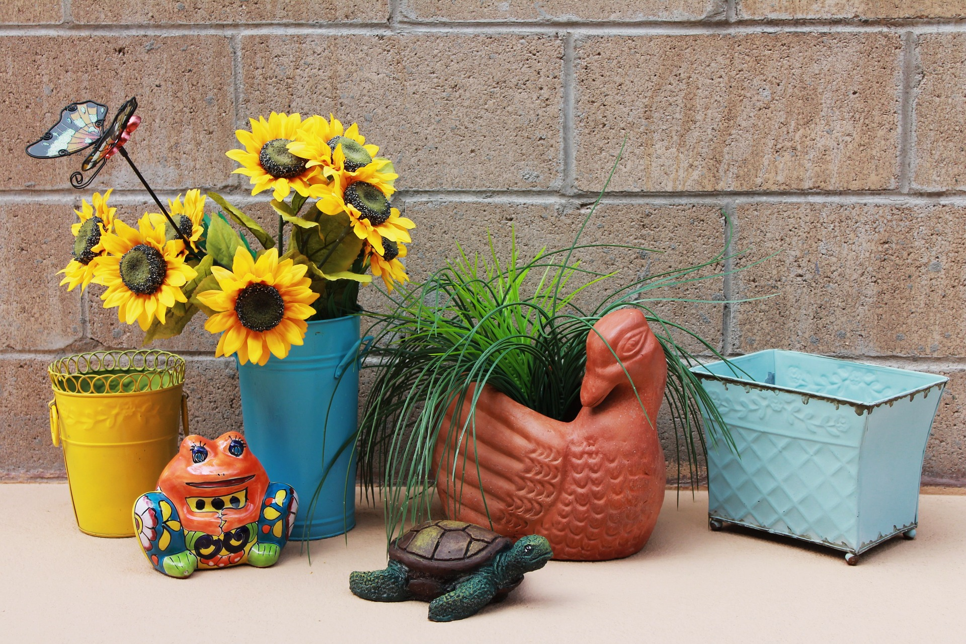 image of cheerful accessories like butterfly, ceramic frog and turtle and brightly colored flower pots